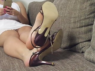 Hanging, shoeplay with jummy high-heel sandals, on sofa.
